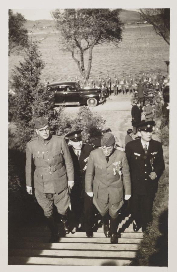 Three uniformed men ascend steps