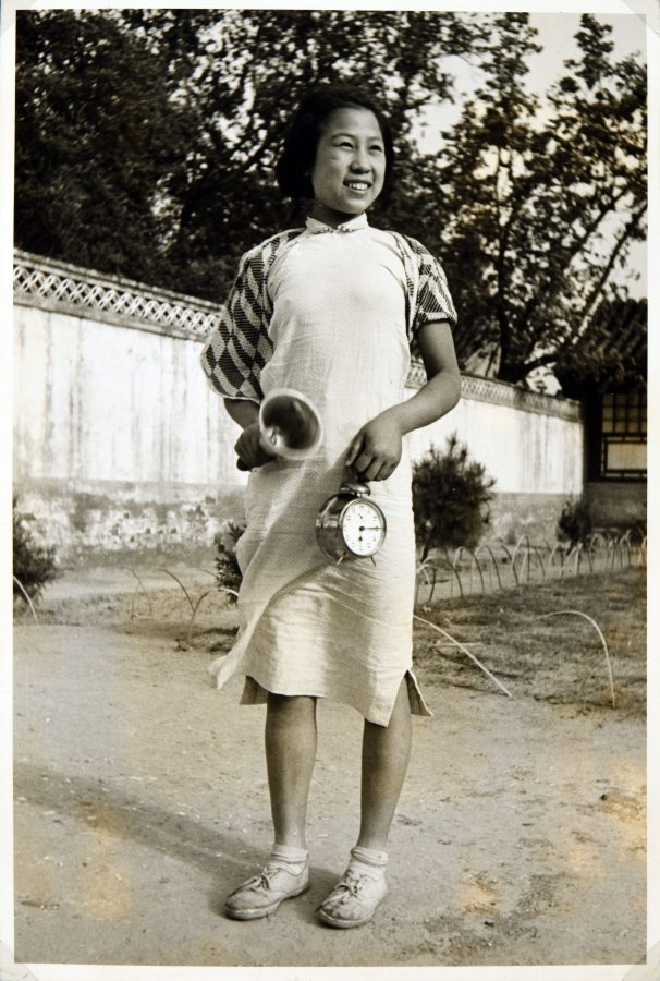 Student at the Peking Jiyu Gakuen School rings a bell and holds a clock.