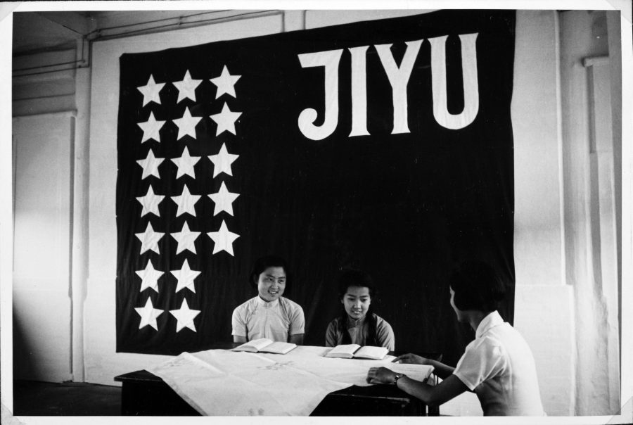 Two Chinese school students take lessons in Japanese beneath the flag of the Peking Jiyu Gakuen.
