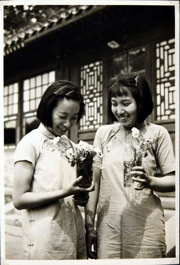 Students at the Peking Jiyu Gakuen School holding cut flowers in glasses.